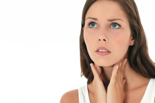 Женщина пальпирует щитовидку